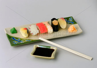 Dish of sushi with chopsticks.