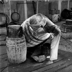 A worker prepares a barrel in the rum plant of Bookers  British Guyana  1958.