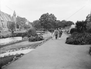 A family walking through a park in Dawlish  Devon  August 1921.
