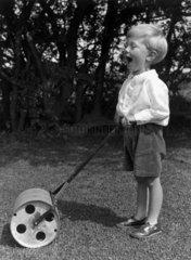 Small boy with a garden roller  c 1930s.
