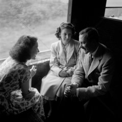 Colin Wills of the BBC talking with two women during a train journey  1950.