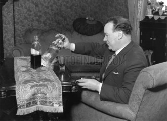 Man siphoning soda into whiskey  23 April 1931.