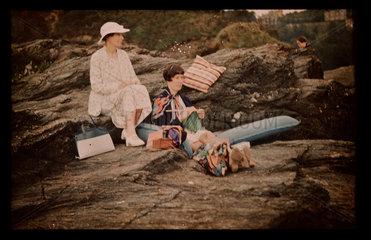 Women sitting on rocks.