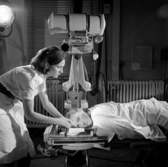 A Royal Free Hospital radiographer sets up patient below scanning machine.