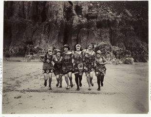 Women running on a beach  c 1925.