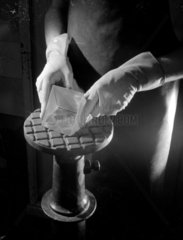 Close up of hands grinding a prism  Grubb Parsons telescopes  1962.