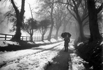 Man with an umbrella standing on a snow-covered country road  c 1920s.