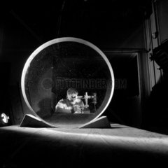 An optical engineer tests a mirror glass for a reflecting telescopes  Grubb Parsons.