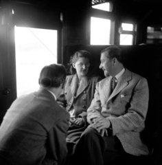 Colin Wills of the BBC talking with a man and a woman in a train carriage  1950.