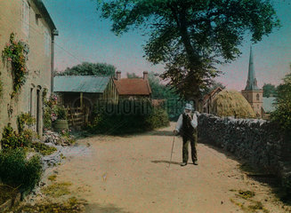 Old man in a country lane  c 1910-1915.