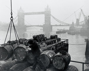 Unloading barrels at London docks  near Tower Bridge  London  c 1930s.