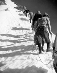Mountaineers ascending a snow-covered peak  1920s.