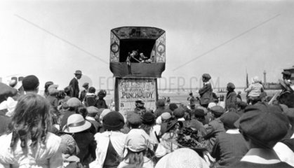 Crowd watching a 'Punch and Judy' show besi