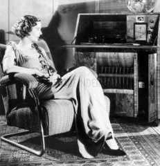 Woman sitting in an armchair listening to t