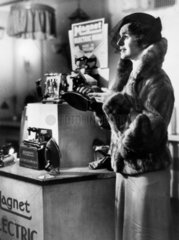 Woman beside a shop display of the latest Magnet electric iron  c 1930s.