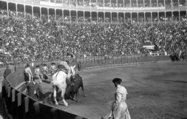 Picador goading a bull with a lance during