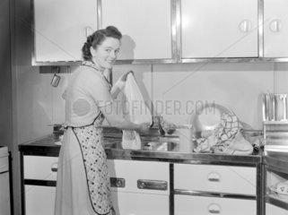 Woman washing cloths in a kitchen sink  1950.