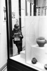 Boy reading comic in an art gallery  1960s.