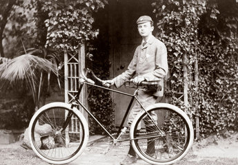 C S Rolls standing with a bicycle  c 1895.