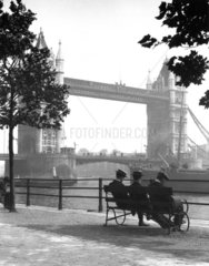 Men sitting by Tower Bridge on the River Thames  London  c 1920s.