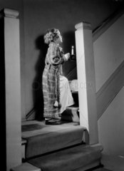 Girl carrying a lighted candle upstairs  c 1948.