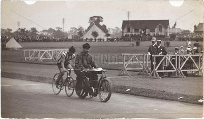 Cyclist being paced by a motorcycle  c 1912.