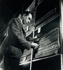 A storekeeper checks piles of cut cloth at Simon Ackerman County Clothes  1948.