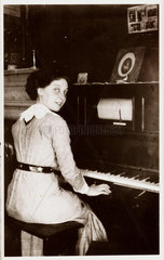 Woman sitting at a player-piano  c 1910.