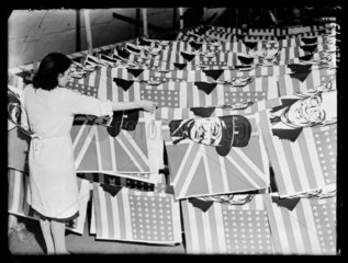 Factory worker laying out flags  1945.