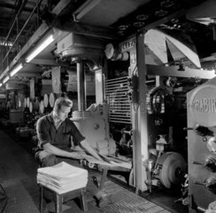 Man at gate of printing machine inspecting newspapers  Bolton  1962.