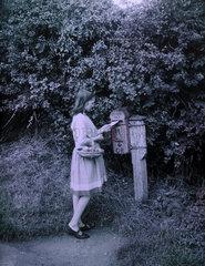 Girl posting a letter  c 1911-1915.