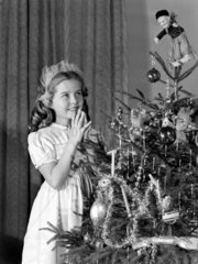 Little girl looking at Christmas tree  c 1950.