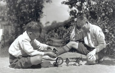 Two boys playing with a Meccano set  c 1930s.