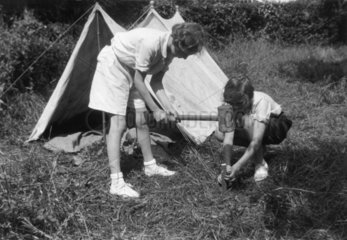 Young girl hammering a tent peg  assisted by her friend  c 1930s.