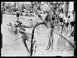 Water fight at an outdoor swimming pool  1937.
