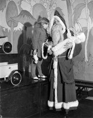 A little girl talking to Father Christmas  23 December 1932.