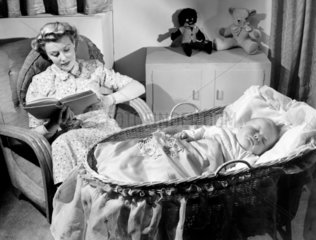 A woman reading as a baby sleeps  c 1949.