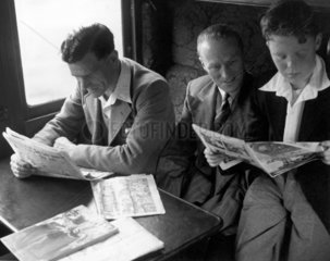 Reading in a railway carriage  c 1950. This