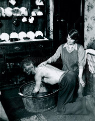 A Welsh miner's wife washing her husband after work  June 1931.