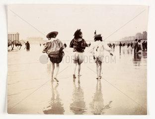 Three girls paddling at the beach  c 1890s.