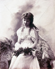 Young woman sitting on fur-covered seat holding a branch of leaves  c 1880-1899.