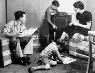 Mother  father and two sons listening to the radio and reading  c 1940s.