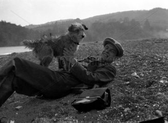 Man playing with a dog in the country  c 1930s.