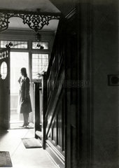 Woman at the front door  England  1920s.