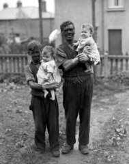 A miner and his family  Rhondda Valley  South Wales  22nd June 1931.