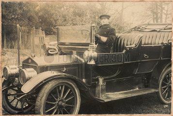 Chauffeur at the wheel of a motor car  c 1905-1920.