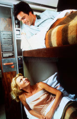 Couple in sleeping carriage bunk beds on BR train  c 1970s.