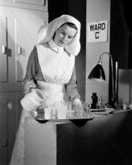 Nurse pouring drinks  c 1950.