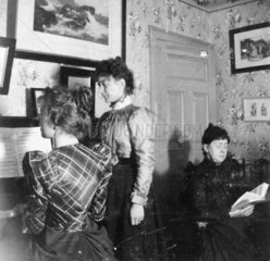 Three woman in a drawing room  c 1890s. Two