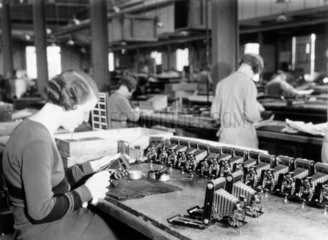 Production line worker assembling a Kodak c